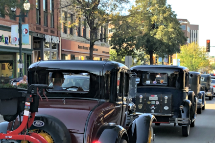A line of Model A's drive through downtown.