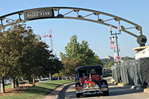 A group of Model A's pass under the arch and entrance to Falls Park in Sioux Falls.