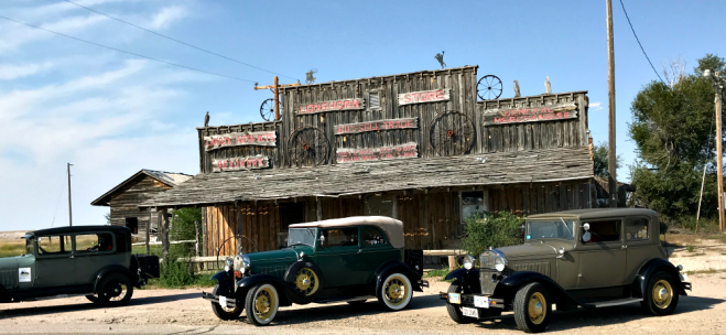 Model A's parked in front of rustic store.